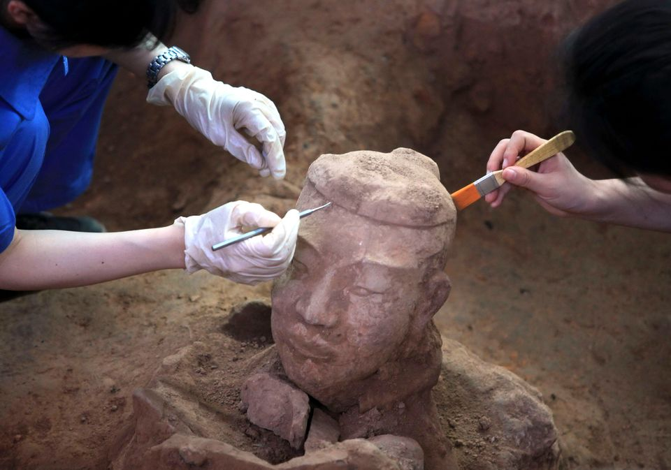 Archaeologists work on a terracotta warrior in the third excavation of pit one at the Terracotta Warriors and Horses Museum i