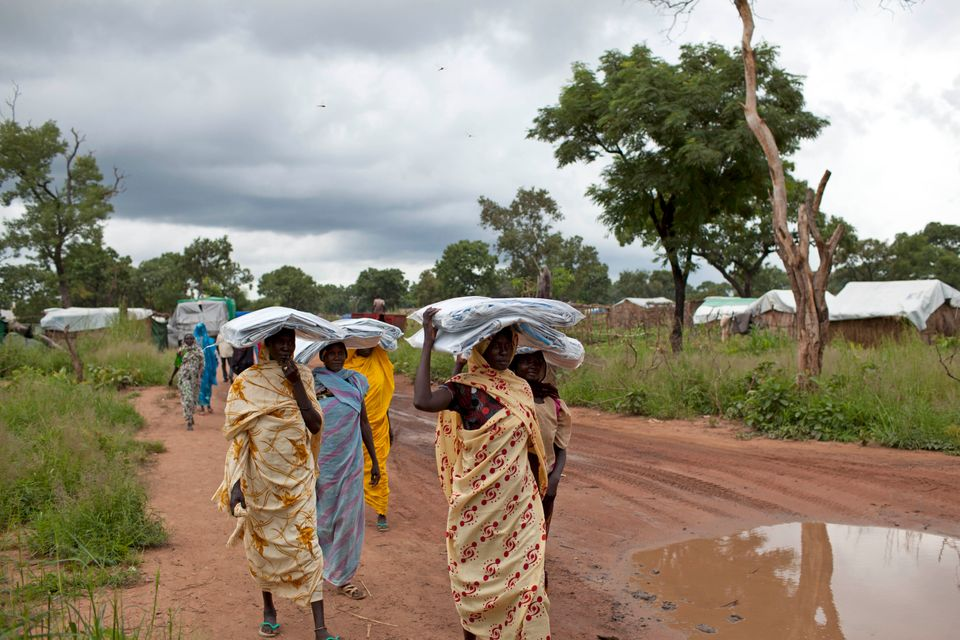 In this photo taken Friday, Sept. 14, 2012, women carry tarpaulin sheets issued by the UN Refugee Agency (UNHCR) back from a