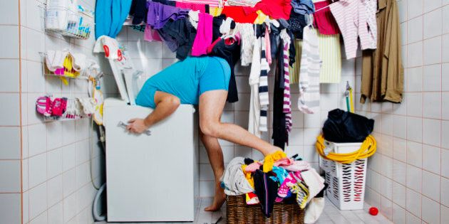 Man repairing the laundrymachine in the bathroom, laundry hanging on a