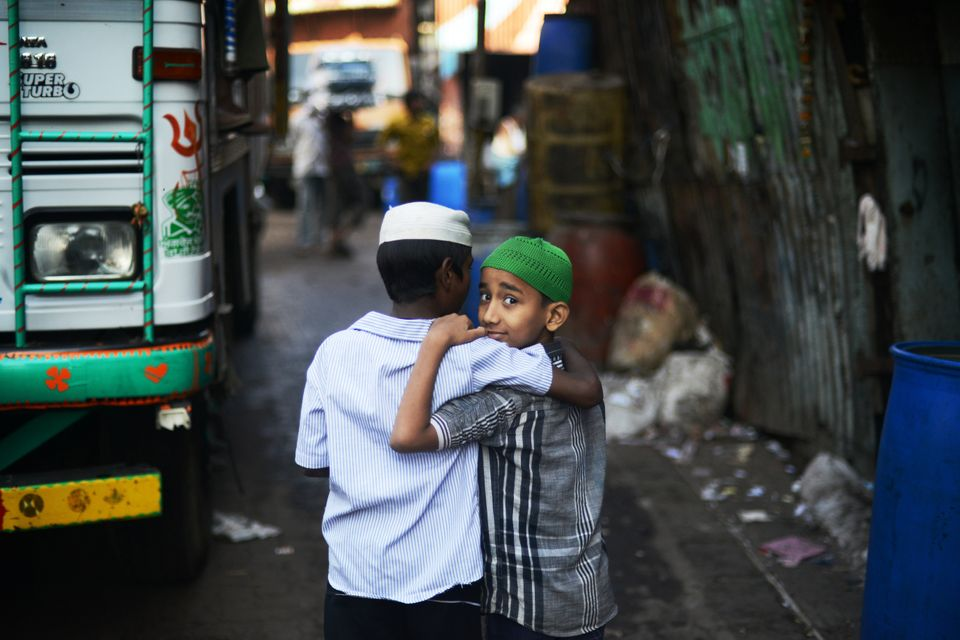 Two Indian boys walk in a back alley in the recycling district of Mumbai's Dharavi slum on December 12, 2012.