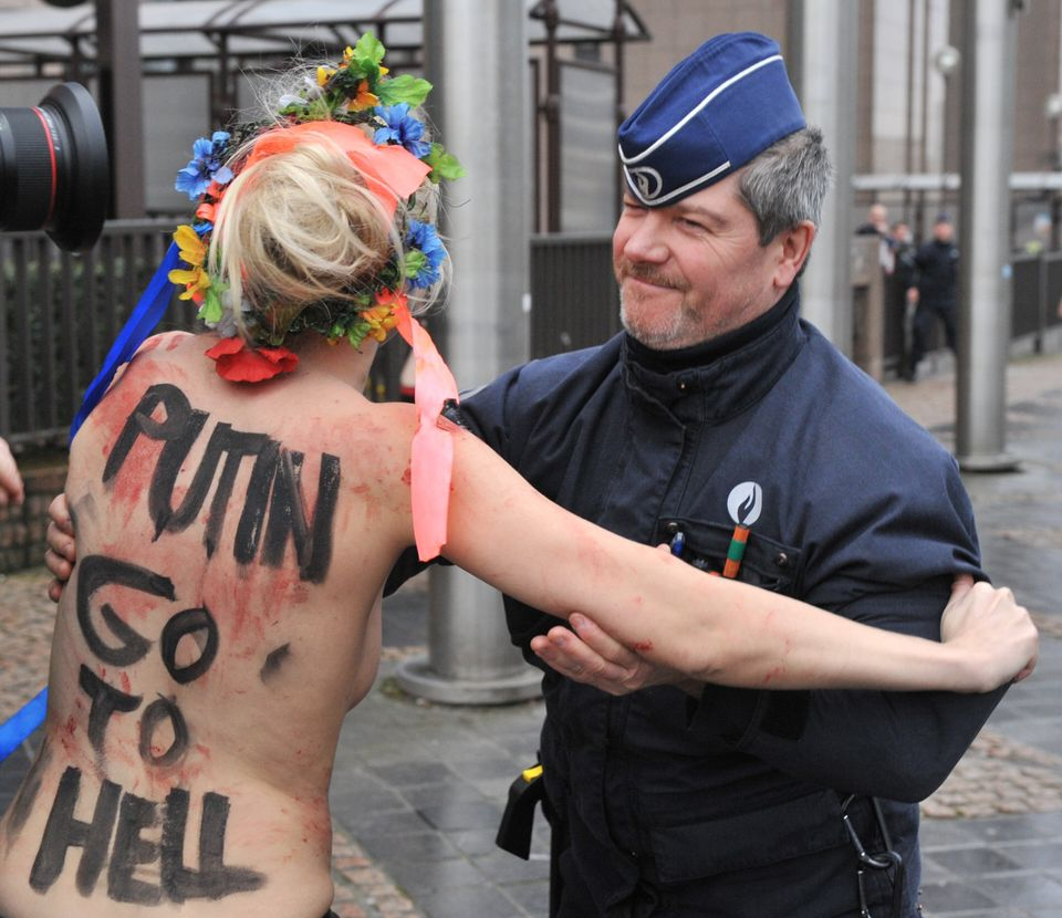 An activist of Ukraine's feminist movement Femen is taken away by the police as she demonstrates by the EU Council building w