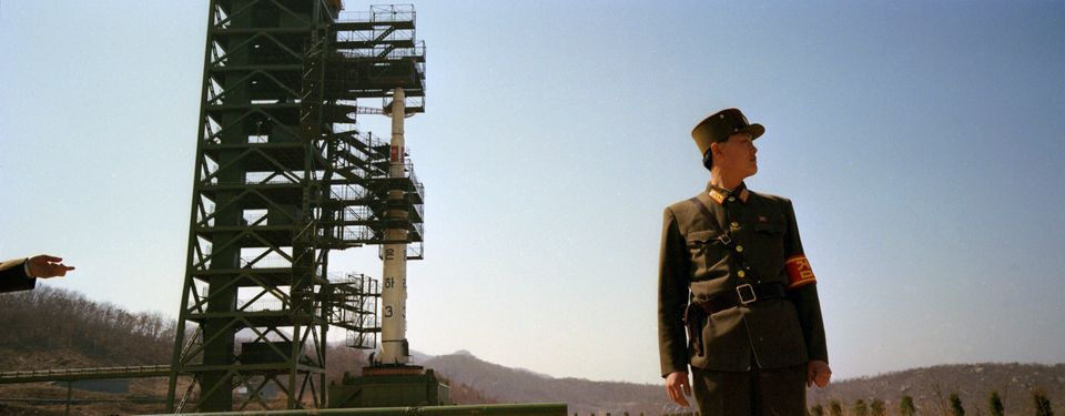 In this April 8, 2012 photo, North Korean soldiers stand guard in front of the country's Unha-3 rocket at Sohae Satellite Sta