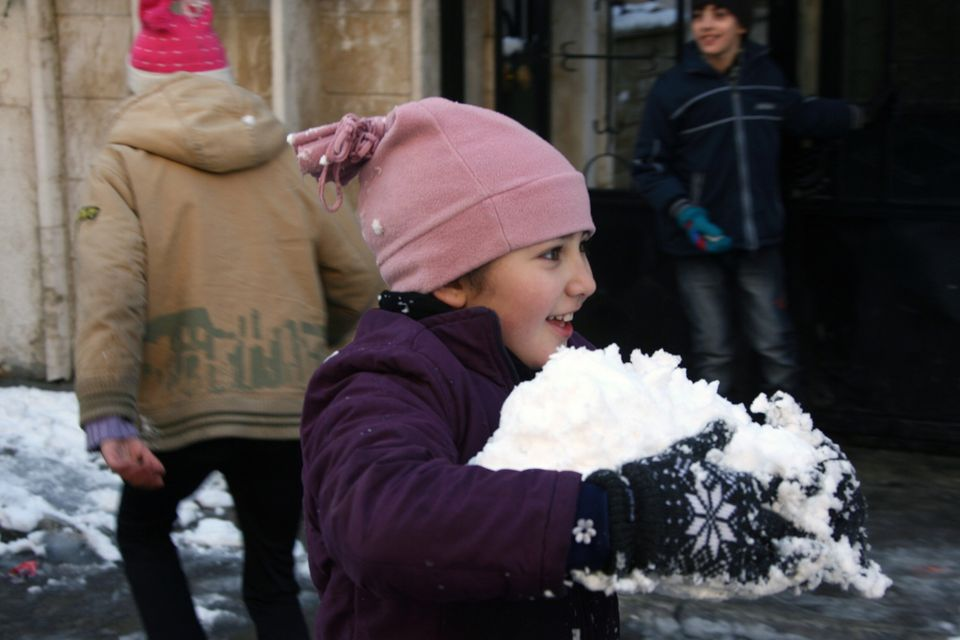 A girl plays with snow on January 10, 2013 in the Syrian capital of Damascus after heavy snow falls. (LOUAI BESHARA/AFP/Getty