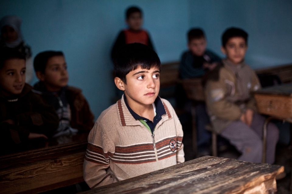 In this Monday, Dec. 17, 2012 photo, a Syrian boy attends class in a village near Aleppo, Syria. School has restarted in some