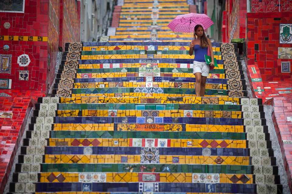 "A woman descends a stairway that was decorated by Chilean artist Jorge Selaron, which he titled the ""Selaron Stairway"" in Rio"
