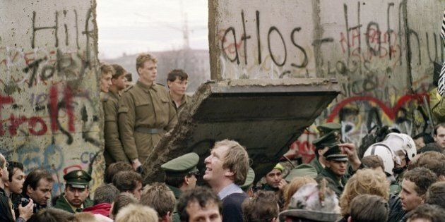 West Berliners crowd in front of the Berlin Wall early 11 November 1989 as they watch East German border...
