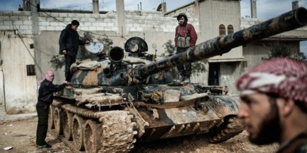 Feb. 23, 2012. A Free Syrian Army member prepares to fight with a tank whose crew defected from government...