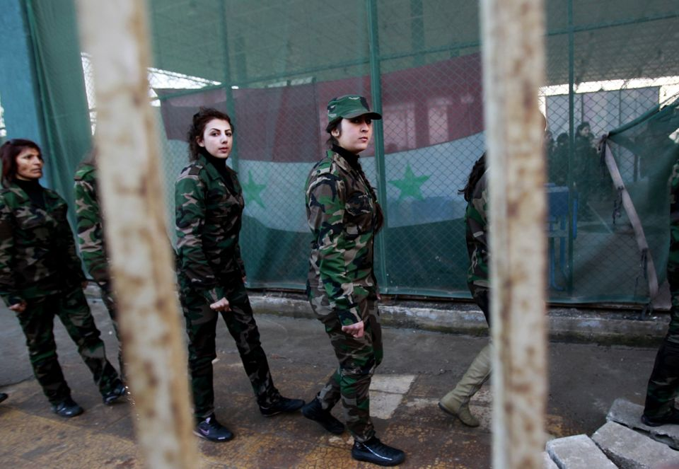Syrian National Defense force women who just finished training, walk in file at a training center in Wadi al-Dahab in the Syr