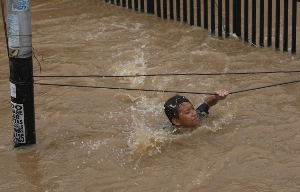 An Indonesian man grabs wires to keep from being swept away by flood water in Jakarta, Indonesia Friday, Jan. 18, 2013. (AP P