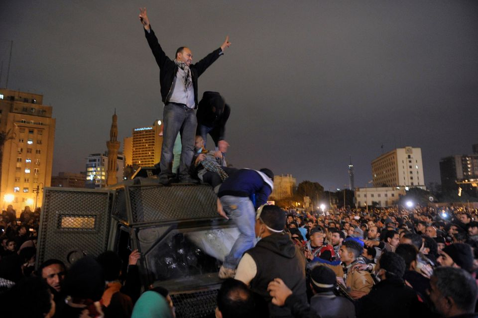 In this Monday, Jan. 28, 2013 photo, Egyptian protesters celebrate the capture of a state security armored vehicle that demon