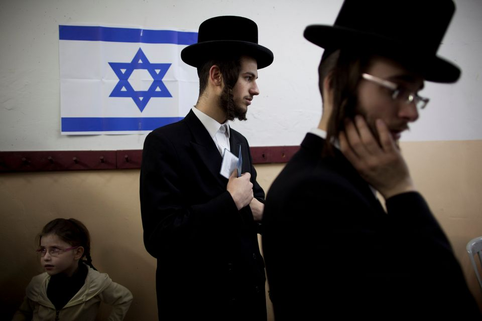 An Ultra-orthodox Jewish man holds his ID card as he waitS to vote in Bnei Brak, Israel, during legislative elections, Tuesda