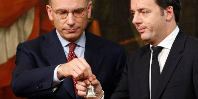 Italian outgoing Premier Enrico Letta, left, hands over the cabinet minister bell to new Premier Matteo...