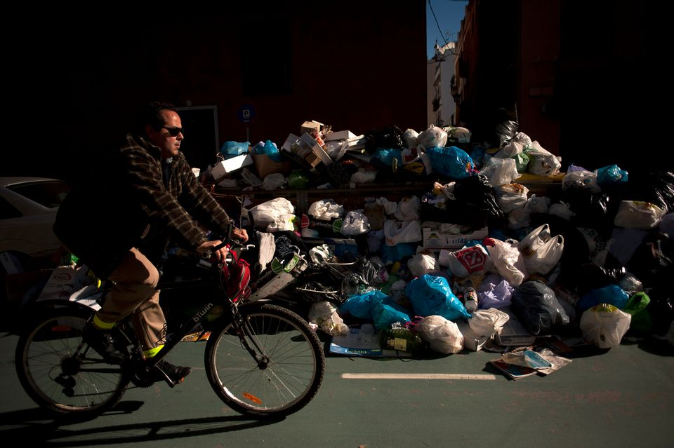 A man rides past uncollected rubbish in a street of Sevilla on February 4, 2013. (Jorge Guerrero/AFP/Getty Images)