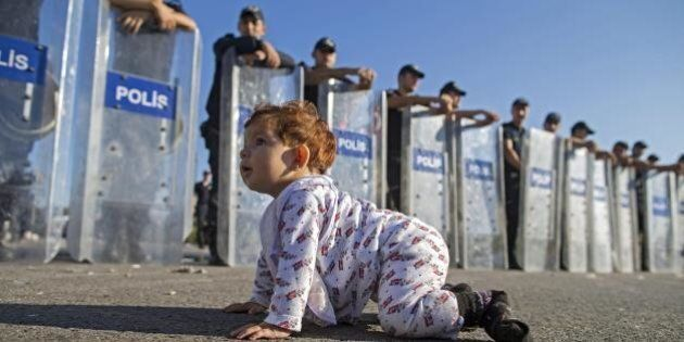 Baby profuga gattona davanti agli agenti con gli scudi. Un'altra foto simbolo della crisi
