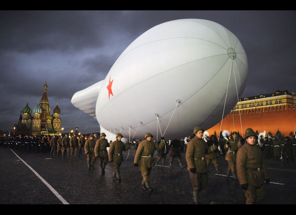 Russian soldiers dressed in World War II uniforms pull a dirigible aircraft during a military parade rehearsal at the Red squ