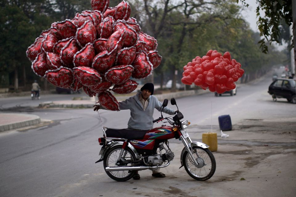 A Pakistani youth pushes his motorcycle, with balloons that he hopes to sell on Valentine's Day, in Islamabad, Pakistan, Thur