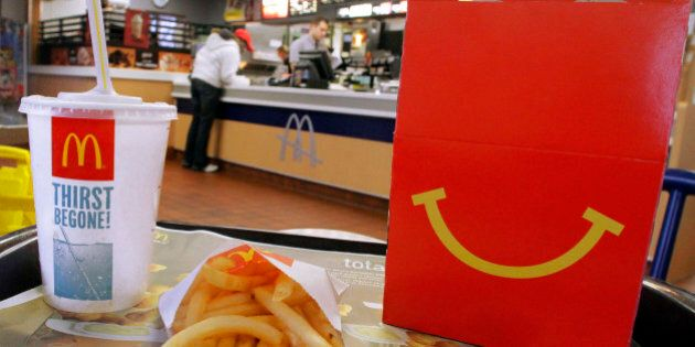 In this Jan. 20, 2012 photo, the McDonald's logo and a Happy Meal box with french fries and a drink are...