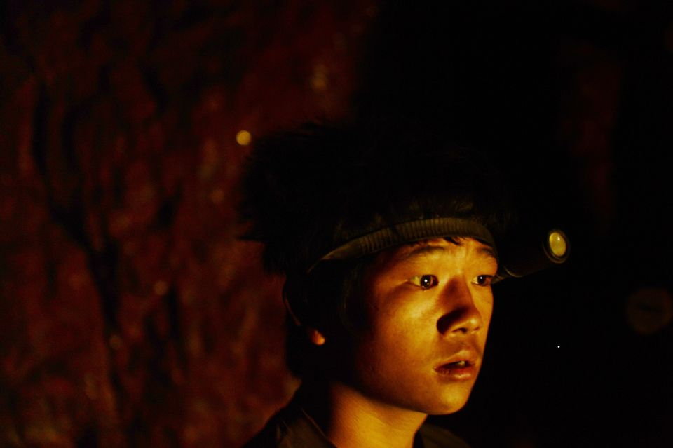 In this photograph taken on January 29, 2013, Indian coal miner, Surya Limu, waits to enter a small opening on the face of a