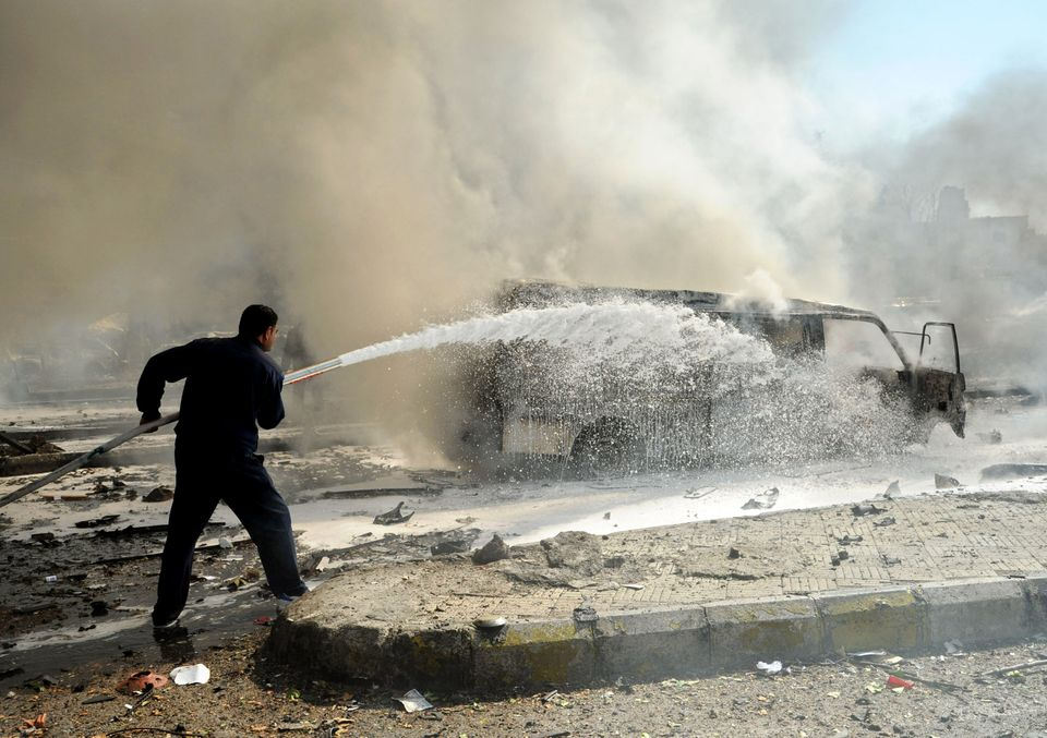 This photo released by the Syrian official news agency SANA, shows a Syrian fire fighter extinguishing burning cars after a h