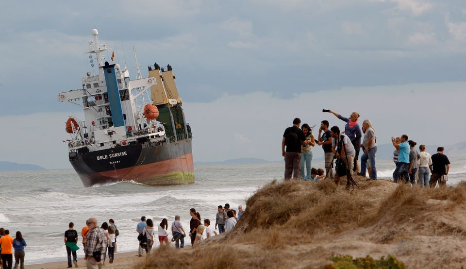 People look at a cargo ship which ran aground after a heavy storm at Saler beach near Valencia Saturday, Sept. 29, 2012. (Pho