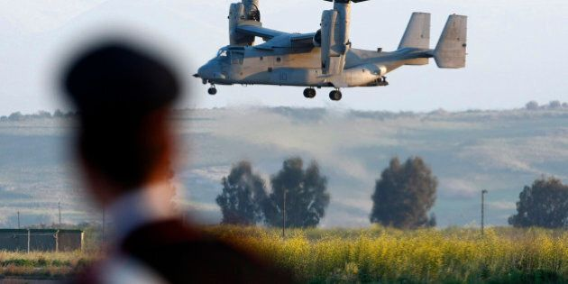 FILE - In this March 24, 2011, an Italian Carabinieri, military police, looks at an MV-22 Osprey carrying...