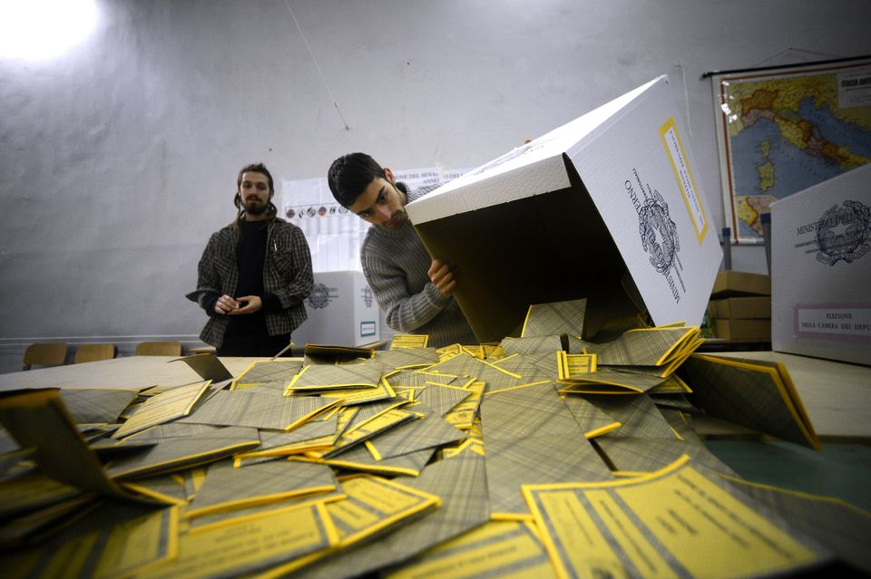 Workers open the ballots in a polling station in downtown Romein a polling station in Rome on February 25, 2013 at the end of