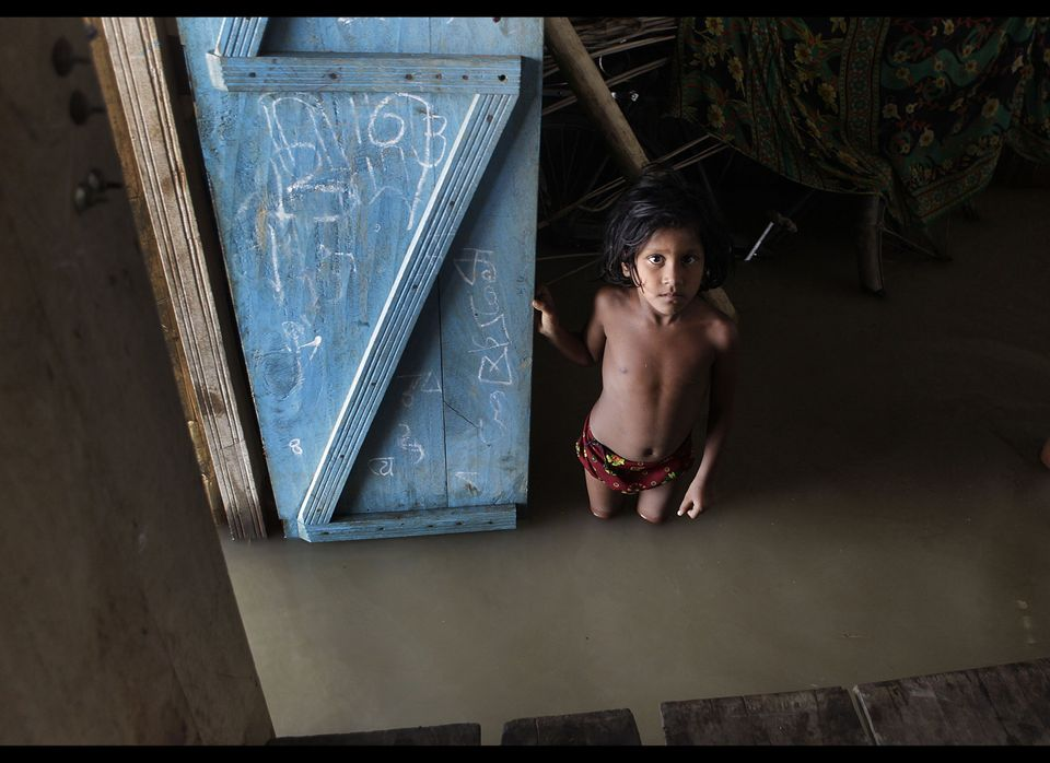 A flood affected child watches from inside her submerged house at Boramari village about 75 kilometers (47 miles) east of Gua