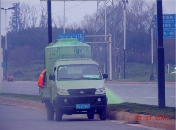 """Chinese workers spray """"Top Green"""" dye on grass in Chengdhu."""