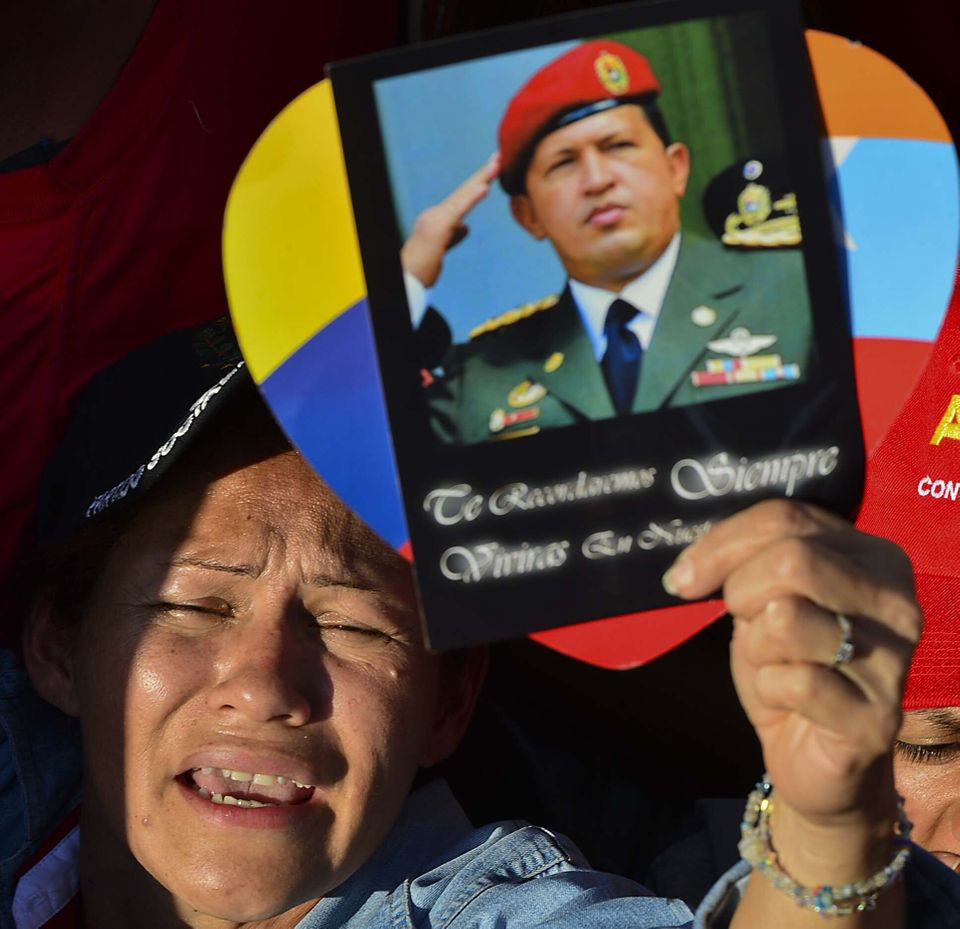 A supporter holds a picture of the late President Hugo Chavez, reading 'We shall always remember. You shall live in our heart