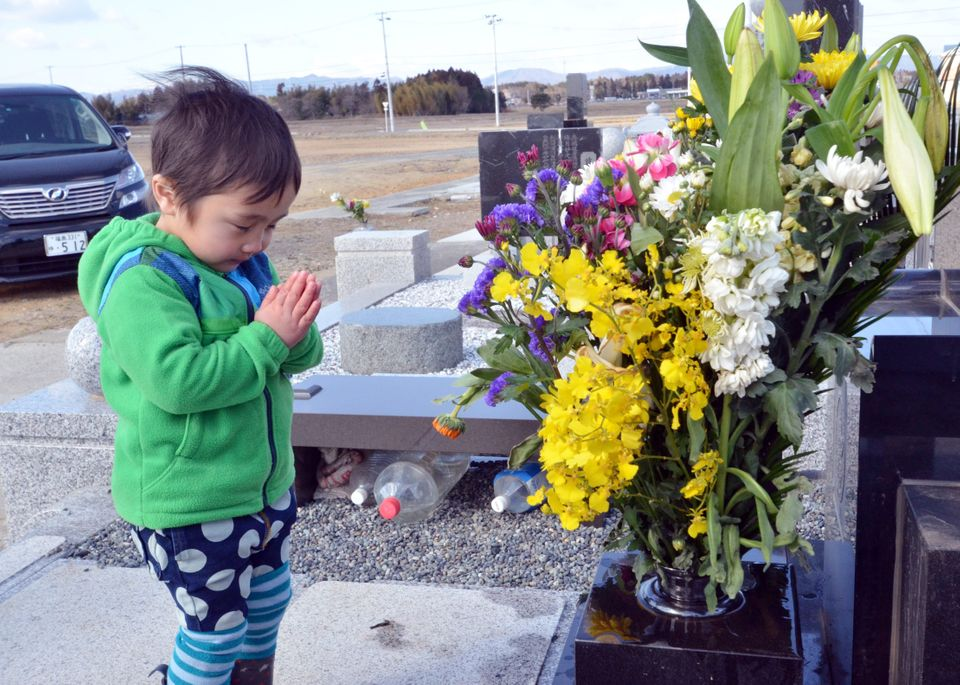 A little boy prays for his relatives killed by the 2011 tsunami at a cemetery in Minamisoma in Fukushima prefecture on March