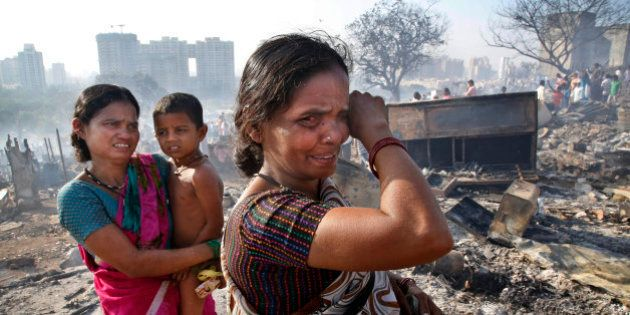 Women cry as they look for reusable household materials after fire broke at slums in Kadivali area of...