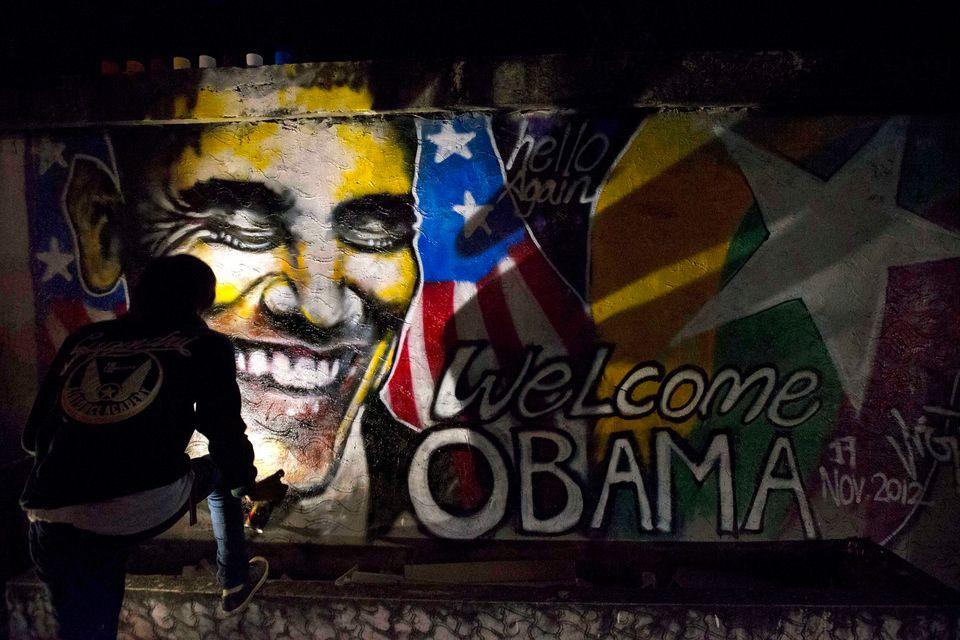 Artist Arker Kyaw paints a graffiti welcoming U.S. President Barack Obama in Yangon, Myanmar, at dawn on Saturday, Nov. 17, 2