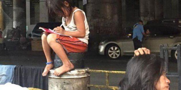 La bambina che studia seduta sulla colonna di un marciapiede