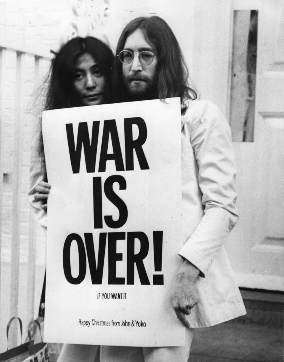 John Lennon (1940 - 1980) and Yoko Ono pose on the steps of the Apple building in London, holding one of the posters that the