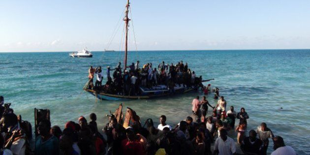 Residents of the Turks and Caicos Islands in the Caribbean assist passengers on an overcrowded sloop....