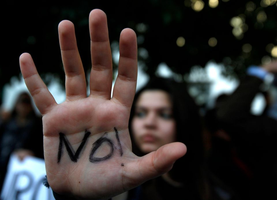 A protestor holds out her hand during a protest outside the parliament in Nicosia, Cyprus, Monday, March 18, 2013. (AP Photo/