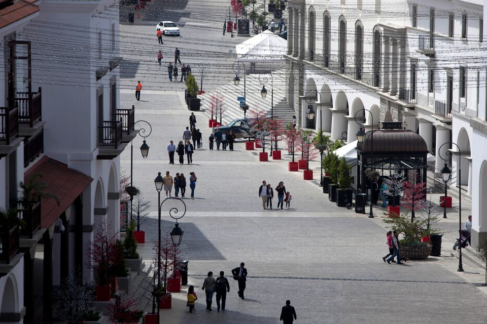 In this Nov. 25, 2012 photo, visitors walk in Paseo Cayala, a nearly independent city on the edges of Guatemala City. Cayala'