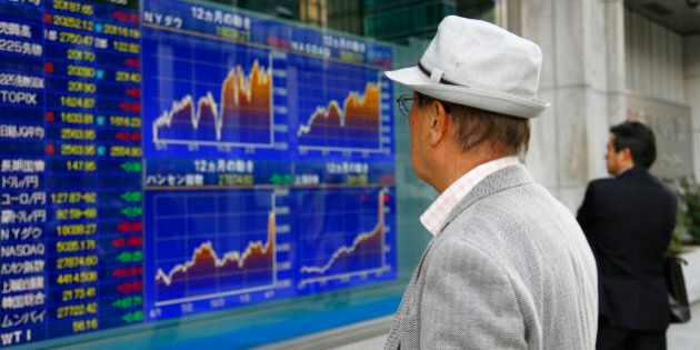 People look at an electronic stock indicator of a securities firm in Tokyo Thursday, April 23, 2015....