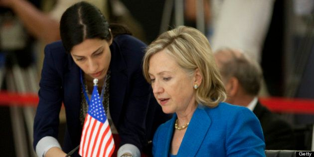 Hillary Clinton, U.S. secretary of state, reads documents with Deputy Chief of Staff Huma Abedin prior...