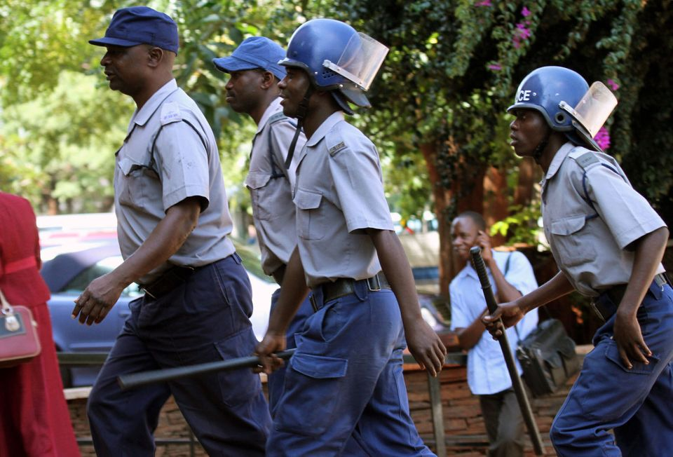 Police armed with batons outside the Harare court where human rights lawyer, Beatrice Mtetwa, unseen, arrived Tuesday, March