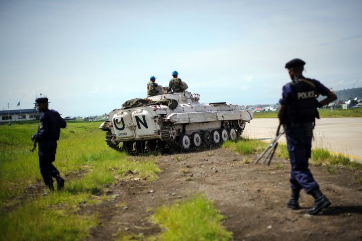 Congolese government policemen walk on December 4, 2012 alongside the runway near to a United Nations armoured personnel carr