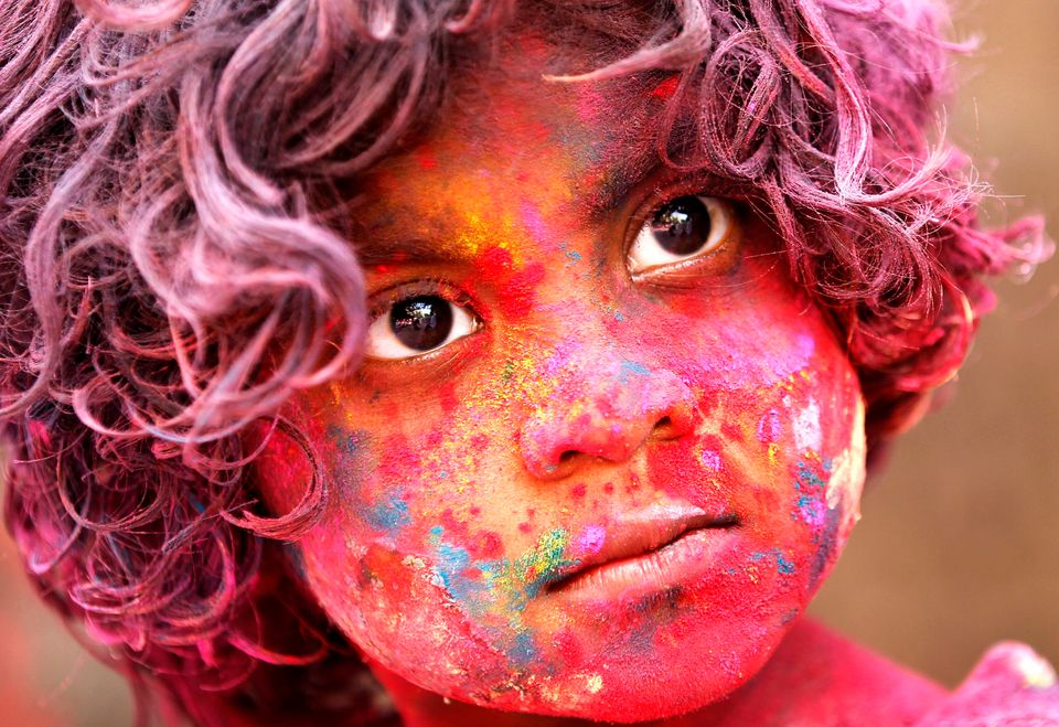 An Indian child, face smeared with colored powder, celebrates Holi festival in Mumbai, India, Wednesday, March. 27, 2013. (AP