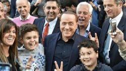 Berlusconi fa le corna dietro la testa di un bambino in una