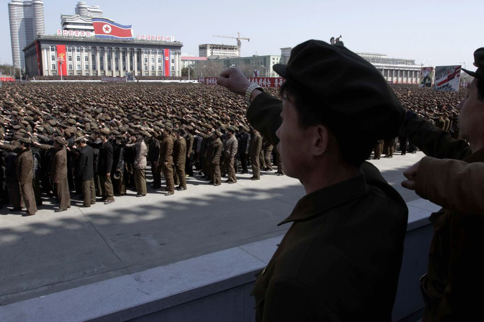 North Koreans punch the air during a rally at Kim Il Sung Square in downtown Pyongyang, North Korea, Friday, March 29, 2013.