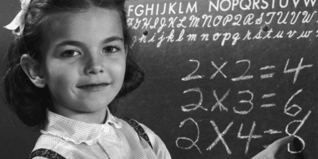 circa 1945: An elementary schoolgirl points to multiplication tables on a blackboard. (Photo by Lambert/Getty