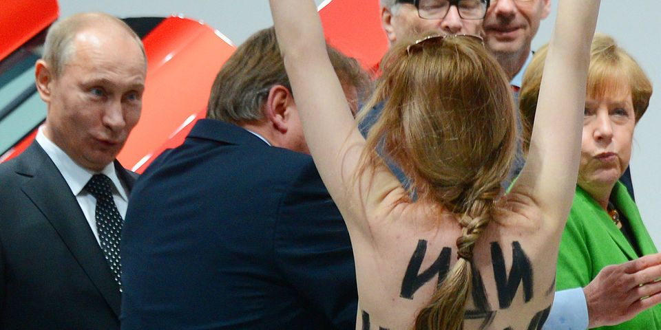 A topless demonstrator with written messages on her back walks towards Russian President Vladimir Putin , left and German Cha