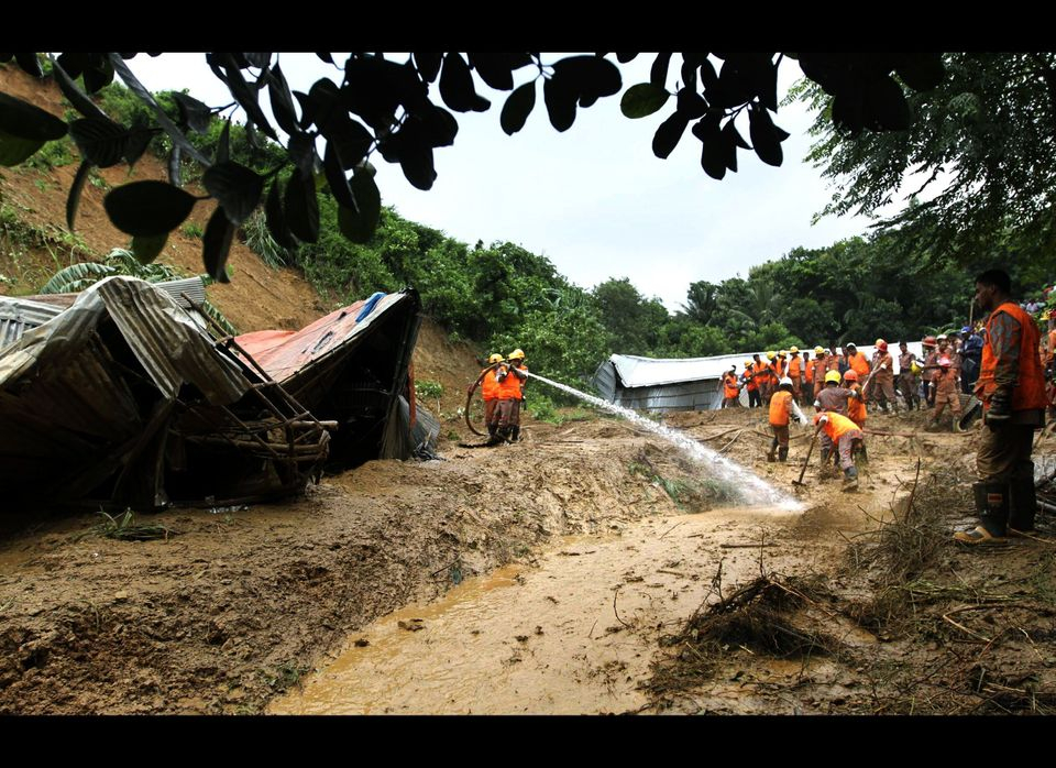 Bangladeshi rescuers search for survivors and bodies following landslides on the outskirts of Chittagong, Bangladesh, Wednesd