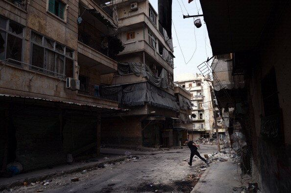 A Syrian rebel fighter runs across a street to avoid snipers of government forces in the Saladin district of the northern Syr