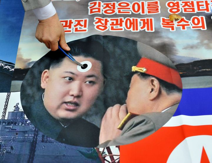 A South Korean activist stabs a pocket knife on a picture of North Korean leader Kim Jong-Un (L) during an anti-North Korea r