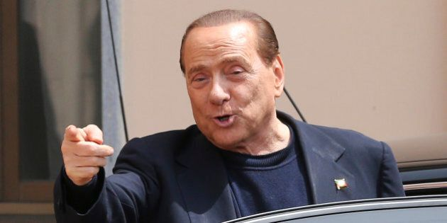 Former Italian Premier Silvio Berlusconi smiles as he leaves